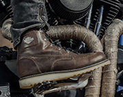 Pair of  mens boots with a motorcycle in the background.