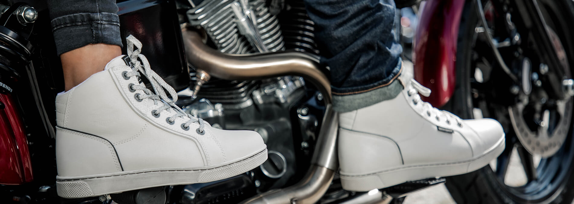 We see the feet of two people sitting on the same bike. They are wearing nice, white shoes.