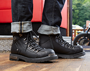 Pair of black mens boots with black soles with a motorcycle in the background.