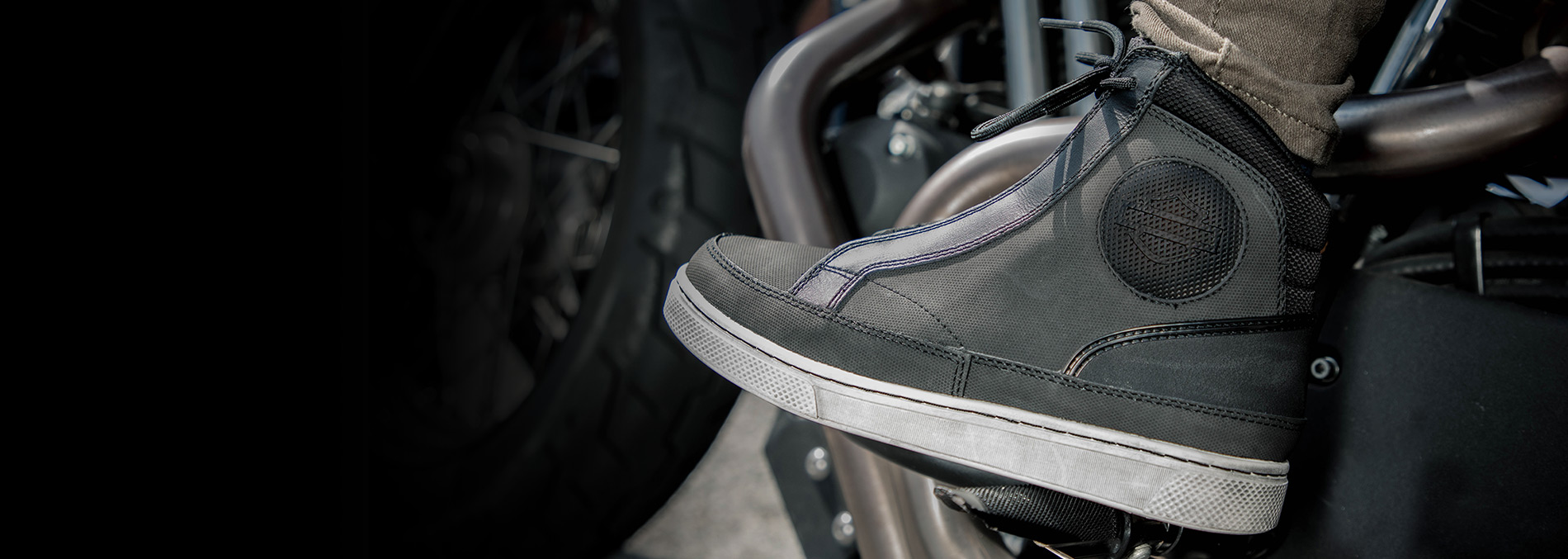 Grey hi-top sneaker, that functions like a boot, worn by a motorcycle rider