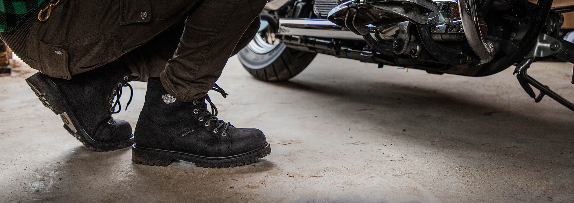 Person wearing hard-wearing boots crouches down beside a motorcycle.