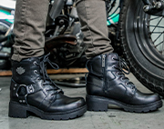 Pair of black womens boots with black soles next to a motorcycle tire.
